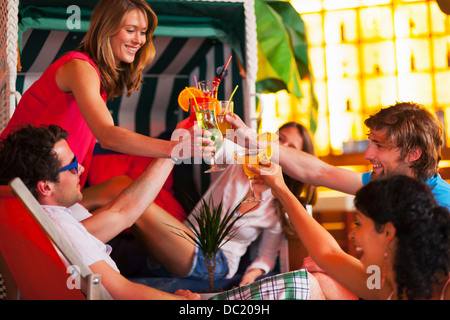 Group of friends with cocktails at indoor beach party - Stock Photo