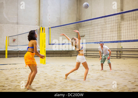 Friends playing indoor beach volleyball - Stock Photo