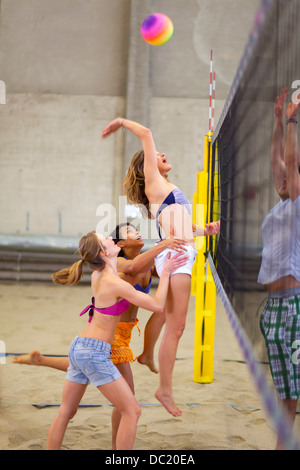 Friends playing beach volleyball at sports centre - Stock Photo