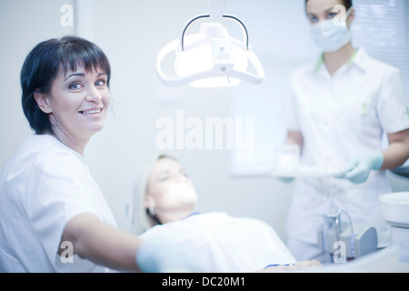 Portrait of female dentist with nurse and patient - Stock Photo