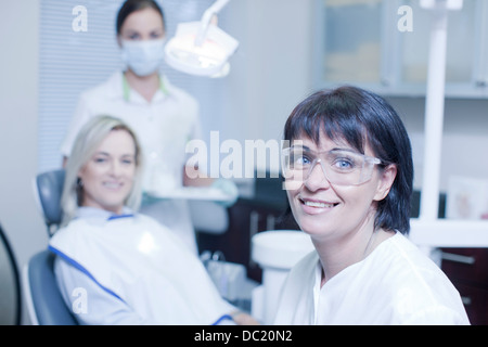 Portrait of dentist with nurse and patient - Stock Photo