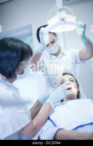 Dentist checking patients teeth - Stock Photo