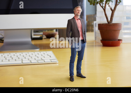 Mature businessman standing on oversized desk - Stock Photo
