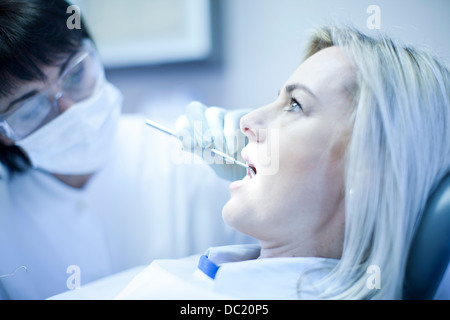 Close up of dentist checking patients teeth - Stock Photo