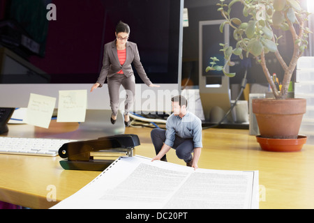 Mid adult business colleagues stapling large document on oversized desk - Stock Photo