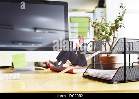 Mature businessman sliding down ruler on oversized desk - Stock Photo