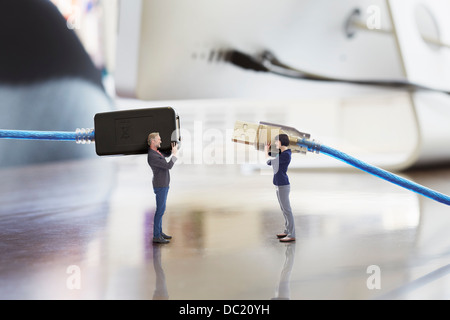 Office colleagues holding large computer cables on oversized desk