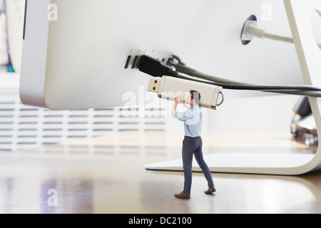 Businessman holding large USB stick next to oversized computer monitor - Stock Photo