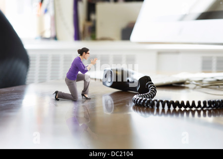 Businesswoman shouting through large telephone receiver on oversized desk - Stock Photo