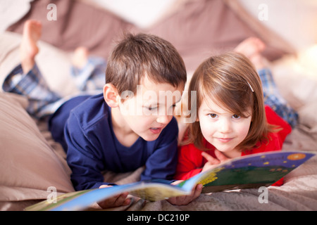 Two young children lying on bed looking at picture book - Stock Photo