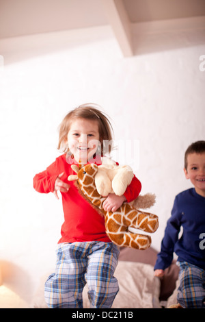 Two young children jumping on bed - Stock Photo
