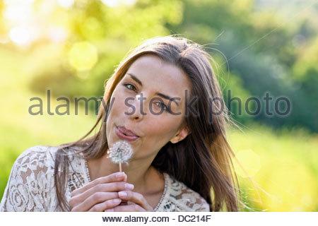 Close up portrait of woman blowing dandelion clock - Stock Photo