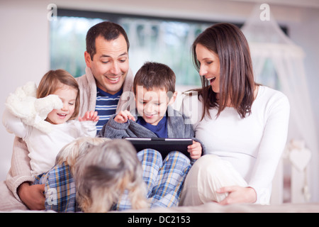Parents, two children and dog looking at digital tablet - Stock Photo