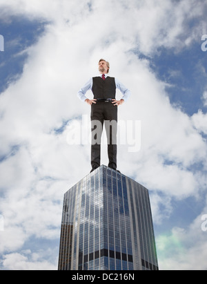 Oversized businessman standing on skyscraper, low angle view - Stock Photo