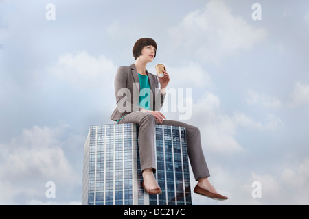 Oversized businesswoman sitting on skyscraper, low angle view - Stock Photo