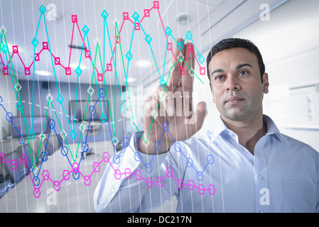 Businessman in office using interactive screen - Stock Photo