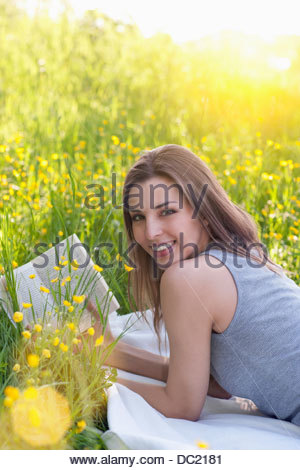 Portrait of young woman reading in field of buttercups - Stock Photo