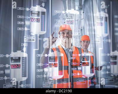 Factory supervisor monitoring product levels on interactive screen - Stock Photo