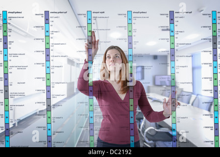 Businesswoman in office using interactive screen - Stock Photo