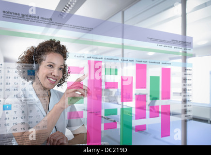 Receptionist booking meeting rooms with interactive screen - Stock Photo