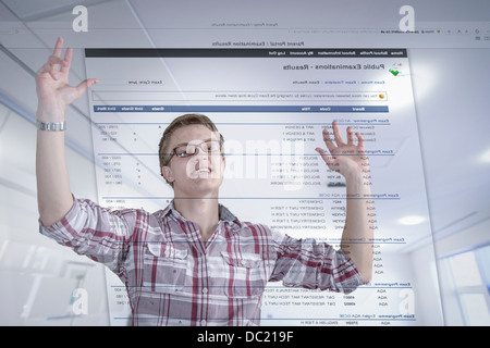 Young student celebrating examination results displayed on screen - Stock Photo
