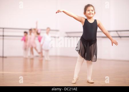 Young ballerina posing in dance studio - Stock Photo