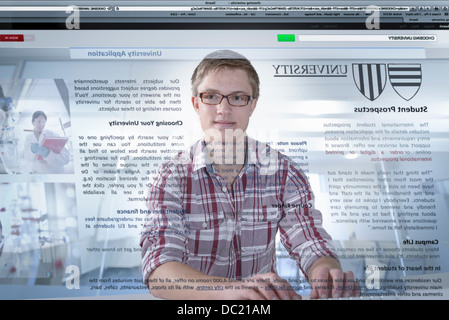 Young student looking at university prospectus on screen - Stock Photo