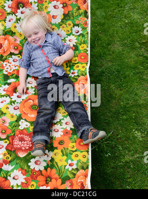 Boy lying on sun lounger, smiling - Stock Photo