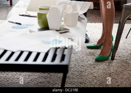 Mature woman in green high heels in office, low section - Stock Photo