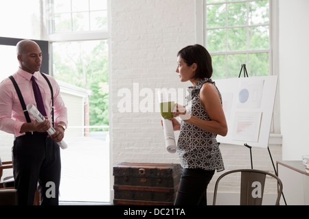 Office colleagues holding rolled up blueprints in meeting - Stock Photo