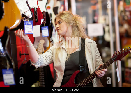 Young women looking at guitars in music store - Stock Photo