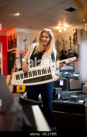 Young woman playing keytar in music store - Stock Photo
