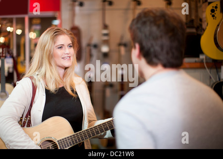 Young couple trying guitar in music store - Stock Photo