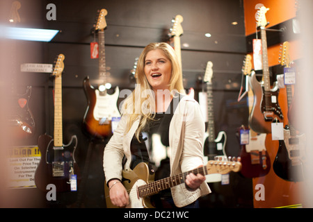Young female testing guitar in music store - Stock Photo