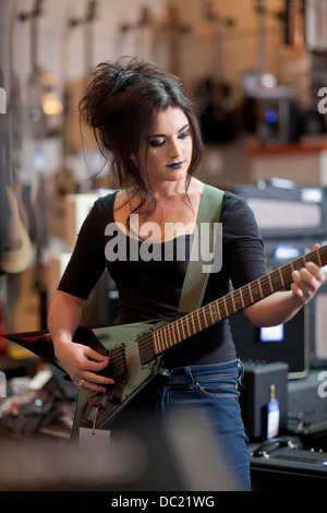 Young woman trying electric guitar in music store - Stock Photo