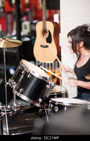 Young woman trying drum kit in music store - Stock Photo