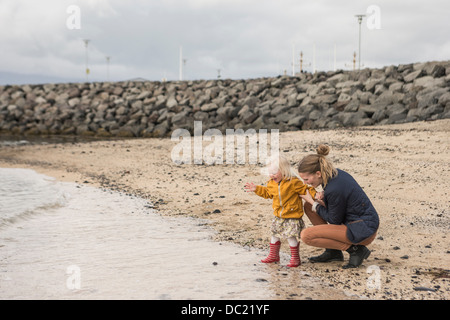 Mother and toddler crouching at waters edge - Stock Photo