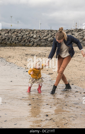 Mother and toddler walking at waters edge - Stock Photo