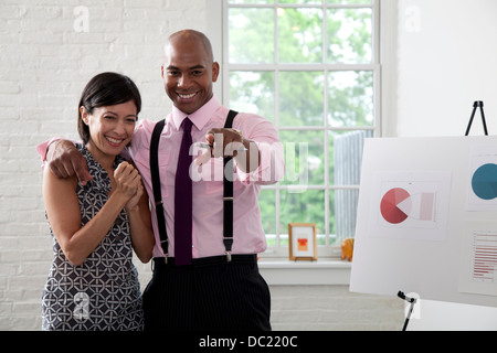 Office colleagues pointing and smiling in meeting - Stock Photo