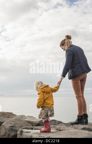 Mother and toddler walking on harbor wall - Stock Photo