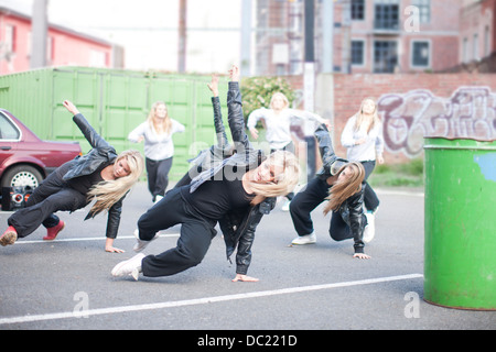 Girls practicing dance moves in carpark - Stock Photo