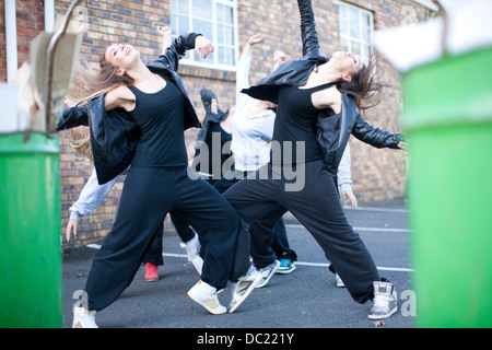 Group of girls dancing in carpark - Stock Photo