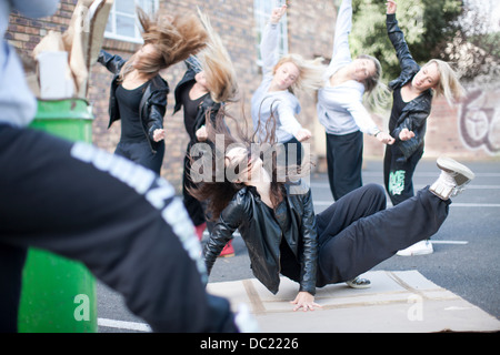 Group of girls breakdancing in carpark - Stock Photo