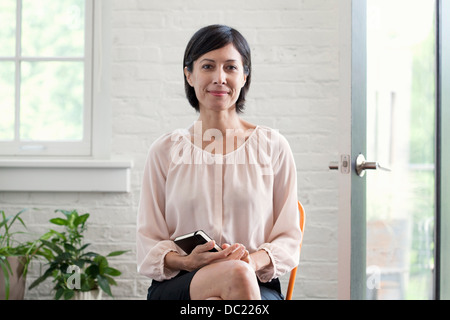 Mature woman holding diary smiling, portrait - Stock Photo