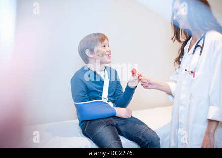 Doctor giving young boy a lollipop - Stock Photo