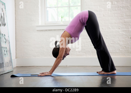 Mature woman performing downward dog yoga position - Stock Photo