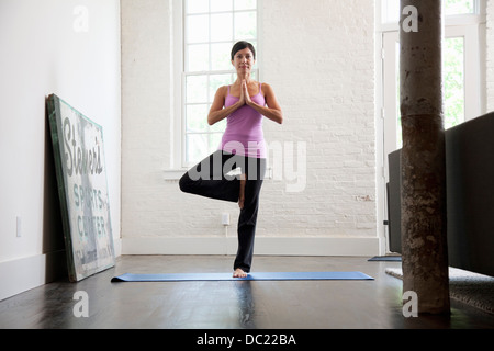 Mature woman standing in yoga position, portrait - Stock Photo
