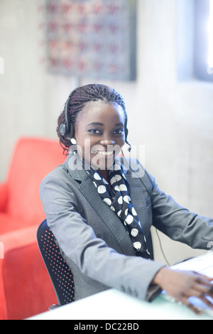 Young woman using telephone headset in office - Stock Photo