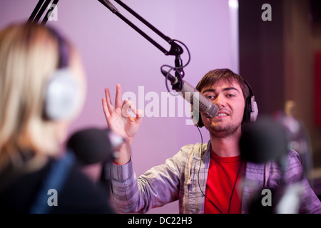Young man and woman broadcasting in recording studio - Stock Photo