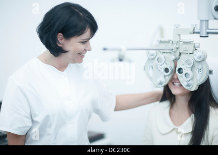 Young woman at opticians having eye test - Stock Photo